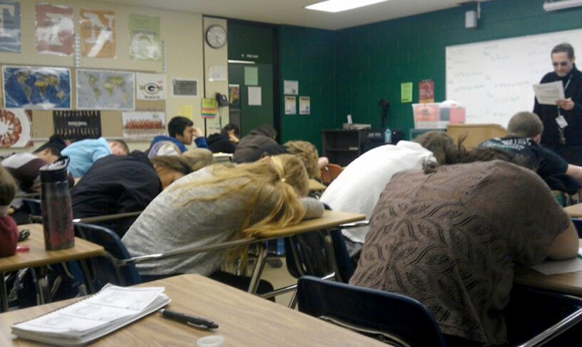One person continues to fight falling asleep during a senior class while the  other have already been taken by senioritis.